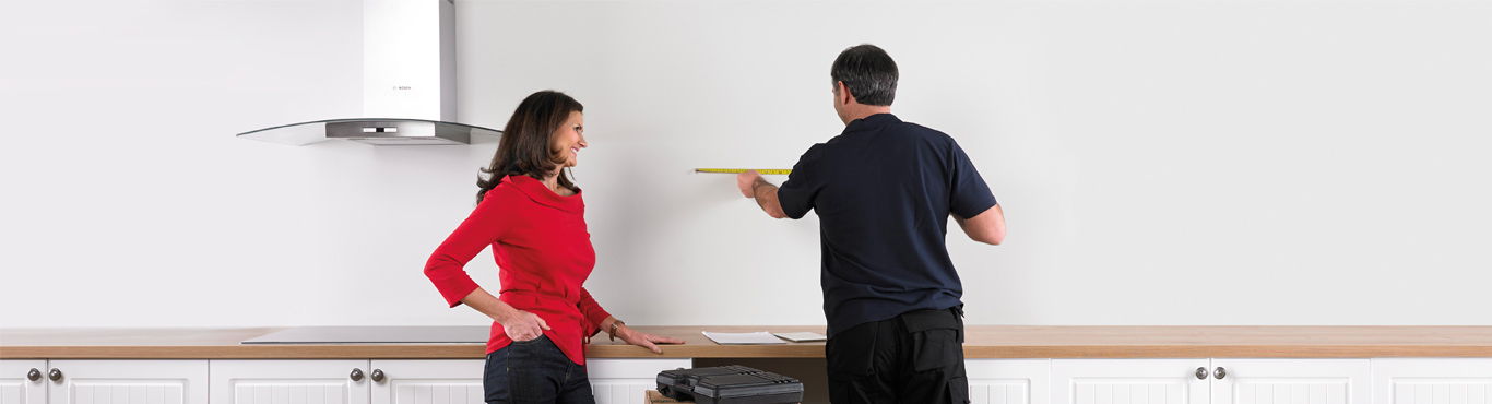 Photo of an installer measuring up a wall with a customer.