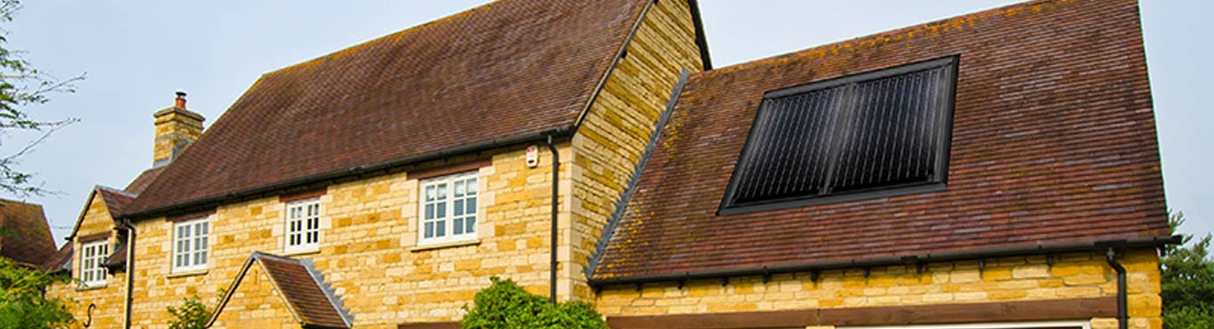 Photo of a country house with a solar panel on the roof.