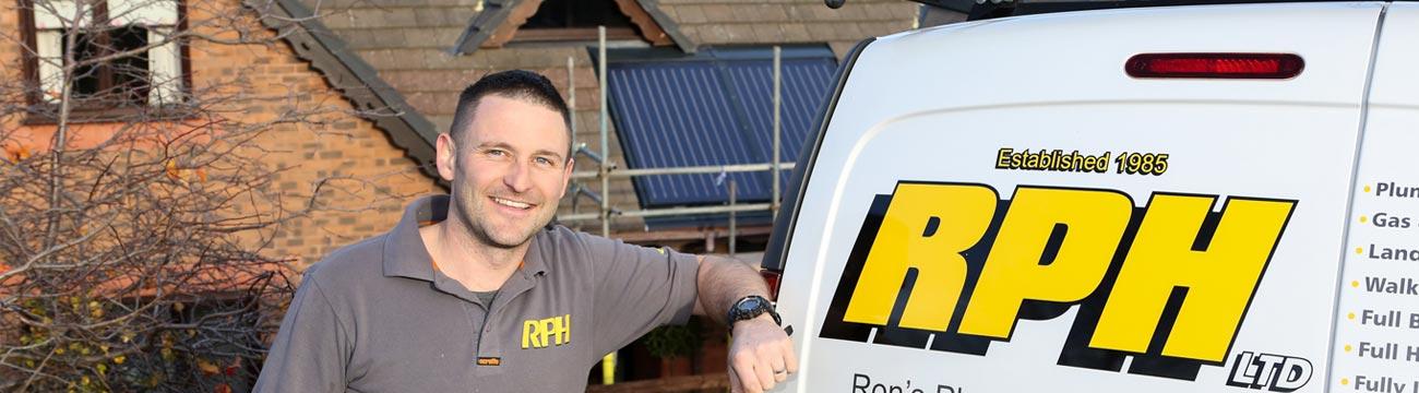Photo of smiling RPH Installer standing next to his van.