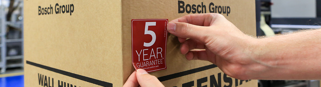 Closeup photo of a Worcester worker putting a 5 year guarantee sticker on a box.
